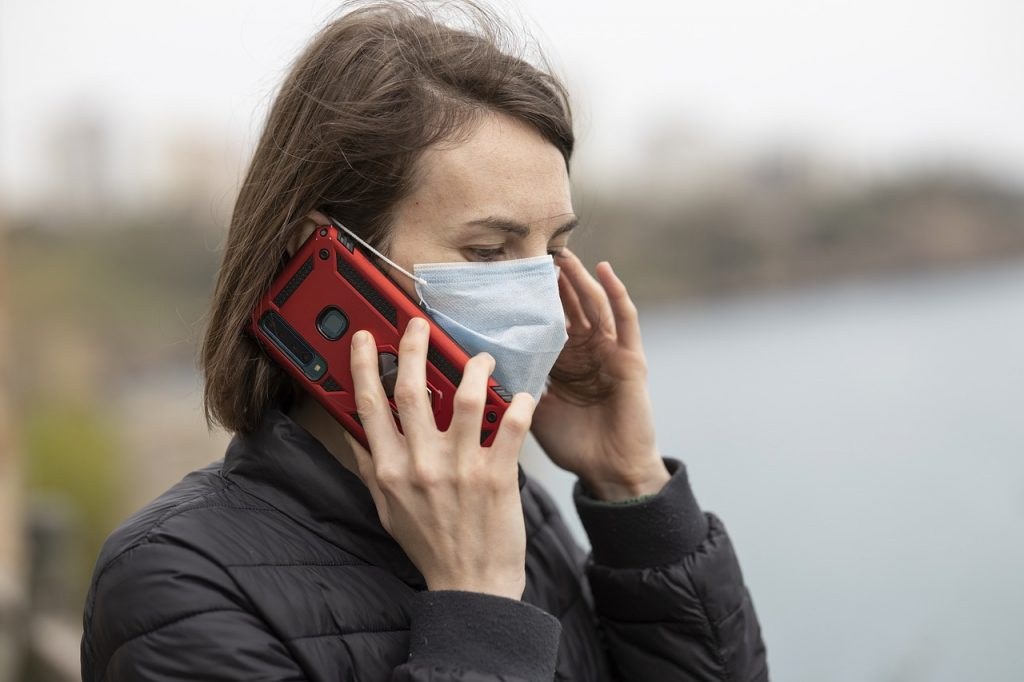 Person wearing a face mask using a phone